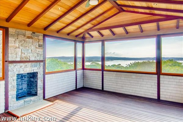 Screened porch with fireplace and water views