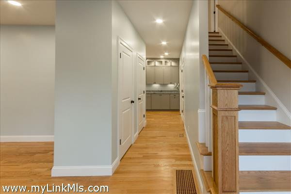 Entryway with soaring ceilings and double coat closets. Door to garage and finished lower level is to near the kitchen on the right
