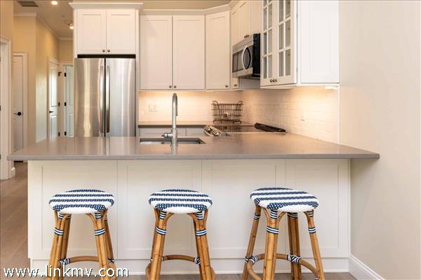 Example of Galley Style Kitchen with Breakfast Bar and Stainless Steel Appliances
