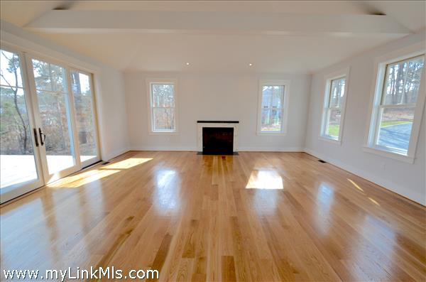 Huge sunfilled great room with gleaming hardwood flooring gas fireplace, lots of glass and 8' sliders to exterior South facing deck.