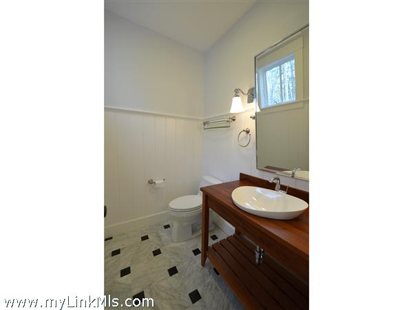 Entry hall powder room with mahogany vanity and marble flooring
