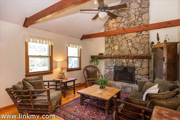 Living Room Has Vaulted Ceilings and Stone Wood Burning Fireplace