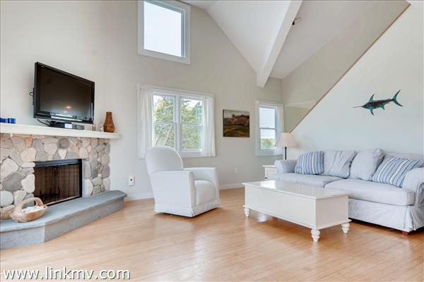 The open bright living room features a stone fire place and views of the water and opens to the deck.