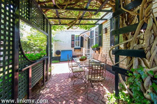 100 Year Wisteria covers one of several outdoor living spaces