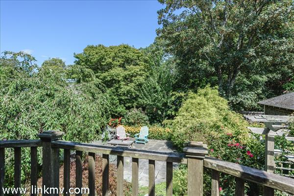 Elevvated deck to the rear of the house overlooks mature plantings and bluestone patio.