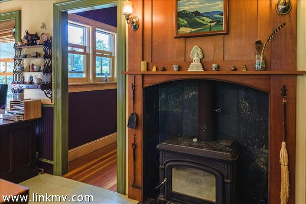 Soapstone wood stove is inserted into soapstone line fireplace in the kitchen.