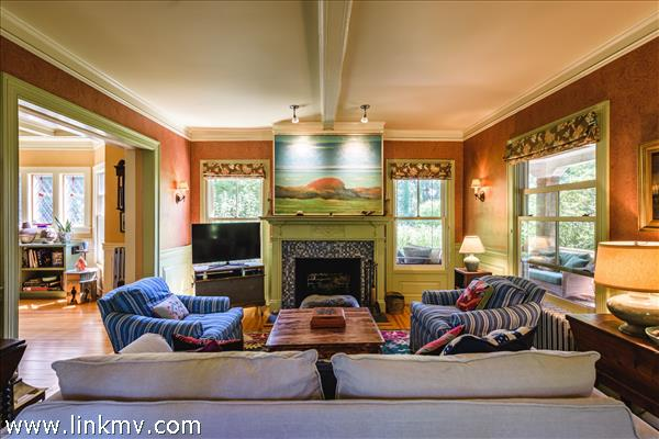 Living room with beamed ceiling, wainscoting and large fireplace