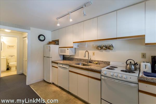 Efficient kitchen with granite counters, stove, microwave, dishwasher and fridge.