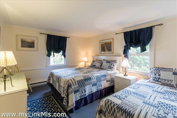 Spacious bedroom with custom roman shades on the large windows.